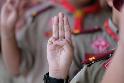 Boy Scout salute of 3 fingers raised on right hand.