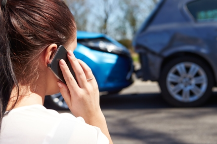 Woman on phone after a rear-end collision with two cars.