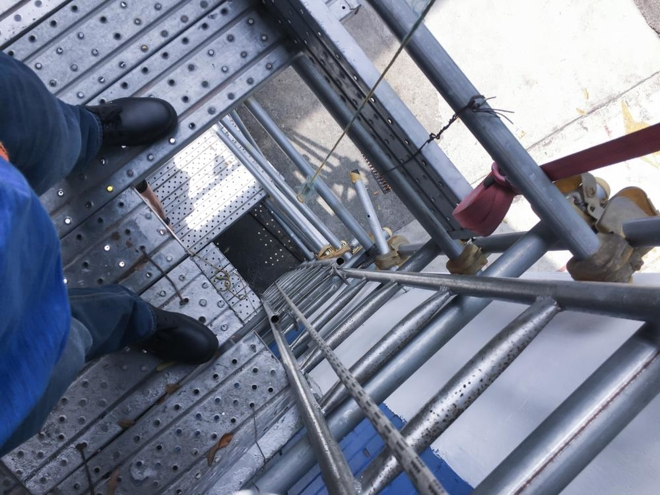 Top view of an opening on the scaffold in a construction site with a metal ladder attached on the guardrail. Guardrails can be used to keep workers from falling.