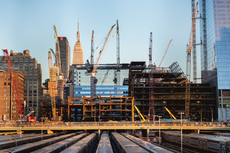 Tall buildings under construction and cranes in New York City. Cranes at site depict active construction projects.
